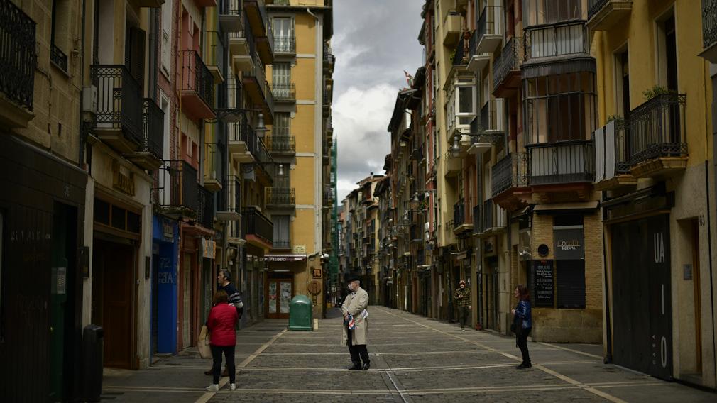 Varias personas hacen cola para comprar pan en la calle Estafeta de Pamplona durante la crisis del coronavirus.