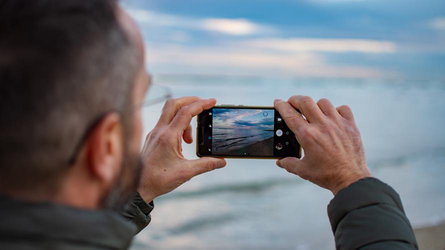 Un turista saca una foto con su teléfono móvil a un lago. DAMIANO LINGAURI