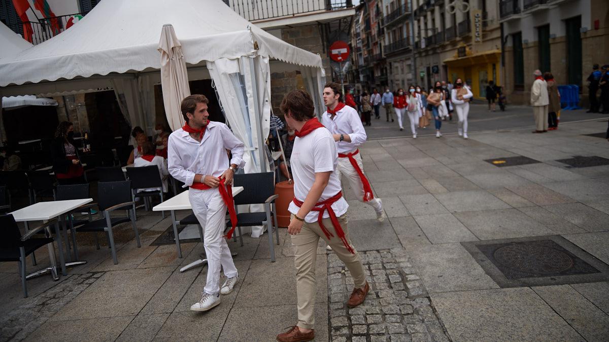 Tres personas vestidas de blanco caminana por la Plaza del castillo de Pamplona durante los no sanfermines de 2021. MIGUEL OSÉS