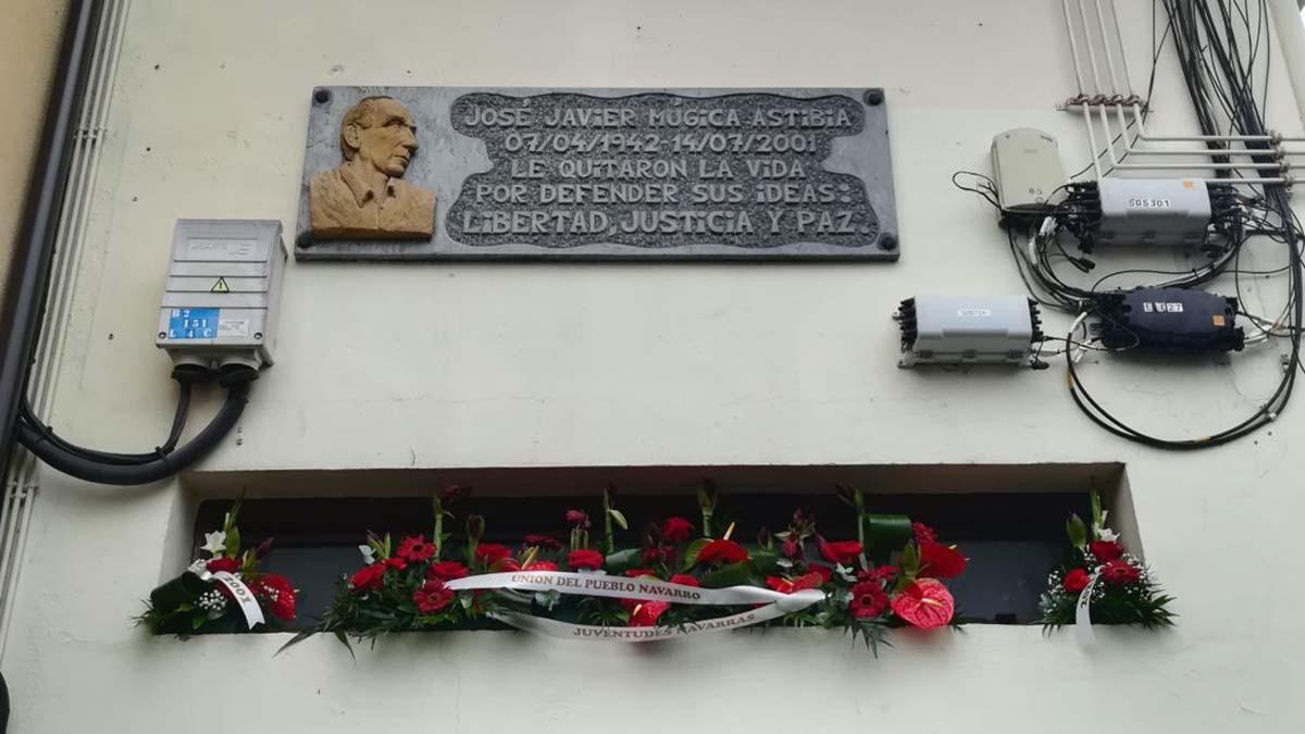 Placa colocada en el lugar en el que fue asesinado por ETA el concejal de UPN, José Javier Múgica, el 14 de julio de 2001. Debajo, un ramo de su partido y de las Juventudes Navarras.