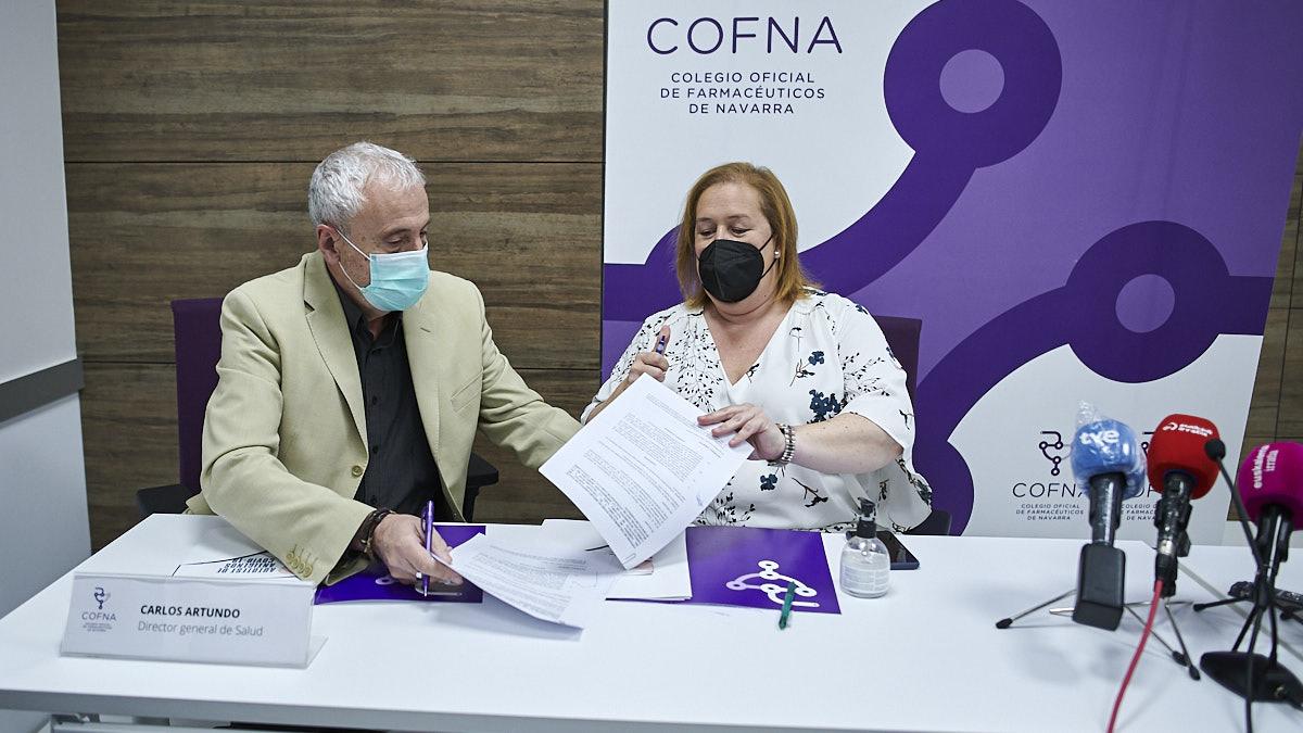 El director general de Salud, Carlos Artundo, y la presidenta del Colegio Oficial de Farmacéuticos de Navarra, Marta Galipienzo, firman un convenio para la realización de autotest de Covid-19 en farmacias. PABLO LASAOSA