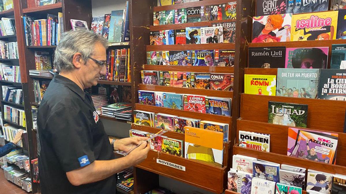 Julio Atienza ordenando algunos de los cómics de la Librería TBO. ARCHIVO